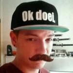Colin met Ok doei. pet (snapback) + snor.