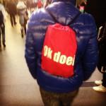 Foto van @ijjvandijk op Instagram van iemand met een Ok doei. sporttas, die ze tegen kwam op Amsterdam Centraal